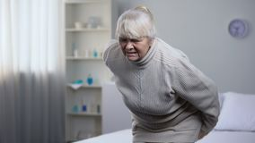 Nurse taking care about old lady suffering from lower back pain, medical center