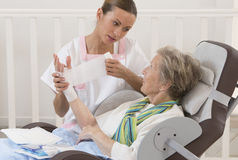 Nurse taking care of senior woman in retirement home royalty free stock photos