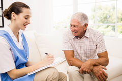 Nurse taking care of sick elderly patient Royalty Free Stock Images