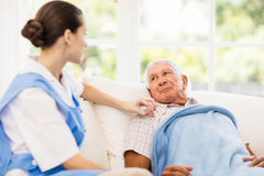 Nurse taking care of sick elderly patient. At home Stock Image