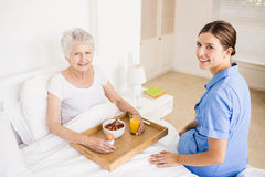 Nurse taking care of suffering senior patient Royalty Free Stock Image