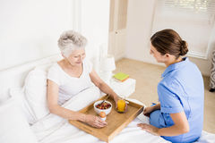 Nurse taking care of suffering senior patient Stock Images