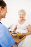 Nurse taking care of suffering senior patient Royalty Free Stock Photo