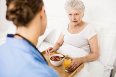 Nurse taking care of suffering senior patient Royalty Free Stock Photos