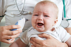 Nurse Taking Crying Baby's Temperature With Digital Thermometer Royalty Free Stock Photography