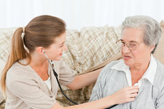 Nurse taking the heartbeat of her patient Stock Images