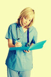 Nurse Taking Notes. Pretty young nurse taking notes stock photography
