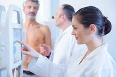Nurse taking scan male patients abdomen Royalty Free Stock Images