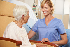 Nurse Taking To Senior Female Patient Seated In Chair Stock Images