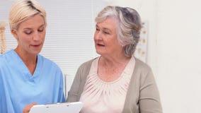 Nurse talking with elderly patient in office stock video