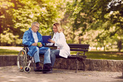 Nurse talking with patient in wheelchair checking up the history. Caring nurse talking with patient in wheelchair checking up the history of the disease Stock Photo