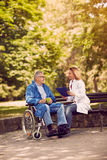 Nurse talking with patient in wheelchair checking up the history. Caring nurse talking with patient in wheelchair checking up the history of the disease outdoor Stock Photography