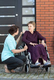 Nurse talking with senior woman on wheelchair Royalty Free Stock Image