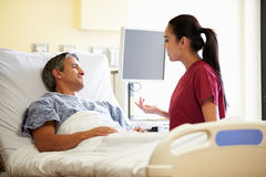 Nurse Talking To Male Patient In Hospital Room. Wearing Scrubs Stock Photos