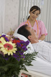 Nurse talking to male patient lying in hospital bed, smiling, side view (tilt) royalty free stock images