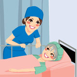Nurse Talking To Patient. Beautiful nurse talking to old senior female patient before having surgery Stock Photography