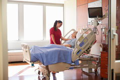 Nurse Talking To Senior Female Patient In Hospital Bed Stock Photography