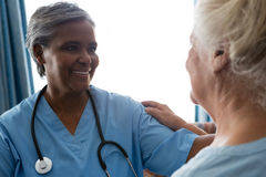 Nurse talking to senior patient in retirement home. Smiling nurse talking to senior patient in retirement home royalty free stock image