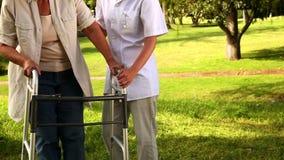 Nurse talking to woman using walker outside