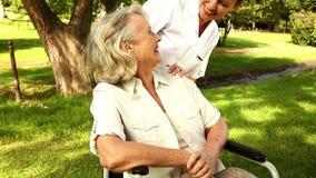 Nurse talking to woman in wheelchair outside