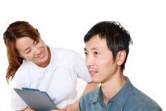 Nurse Talks To Her Patient Stock Photo