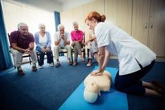 Nurse teaching first aid to a group of seniors stock photo