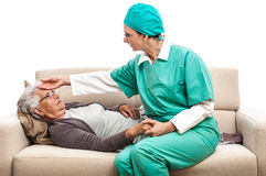 Nurse temperature check old woman laying at bed Stock Photos