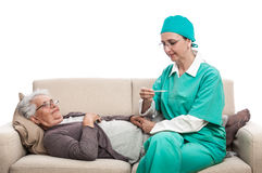 Nurse temperature check old woman laying on sofa Stock Images
