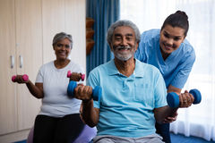 Nurse training seniors in lifting dumbbells at nursing home. Portrait of nurse training seniors in lifting dumbbells at nursing home Stock Images