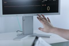 Nurse turning off electrocardiogram. Close-up on nurse turning off electrocardiogram after patient's death Stock Image