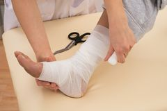 Nurse tying bandage on patient's foot Royalty Free Stock Photography