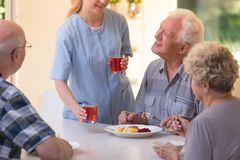 Nurse giving juice to seniors Royalty Free Stock Photo