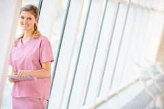 Nurse Using Digital Tablet In Corridor Of Modern Hospital Royalty Free Stock Images