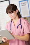 Nurse Using Digital Tablet At Nurses Station Stock Images