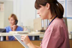 Nurse Using Digital Tablet At Nurses Station Stock Image
