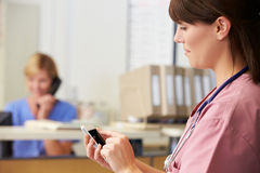 Nurse Using Mobile Phone At Nurses Station Royalty Free Stock Photography