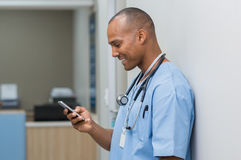 Nurse using phone. Portrait of happy male nurse reading message at mobile phone. Young african surgeon text messaging through cell phone. Man using smart phone stock photography