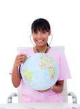 Nurse using stethoscope on a globe Royalty Free Stock Photos