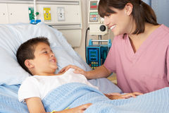 Nurse Visiting Child Patient On Ward Stock Photo