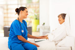 Nurse visiting patient. Friendly nurse visiting recovering senior patient Stock Image
