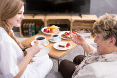 Nurse visiting patient at home. Young nurse visiting senior patient at home royalty free stock photo