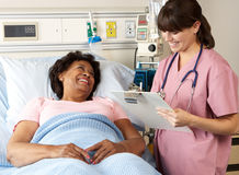 Nurse Visiting Senior Female Patient On Ward Royalty Free Stock Photos