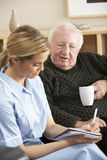 Nurse visiting senior man at home Royalty Free Stock Image