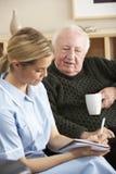 Nurse visiting senior man at home Royalty Free Stock Image