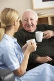 Nurse visiting senior man at home Royalty Free Stock Photos