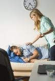 Nurse waking up surgeon Stock Images