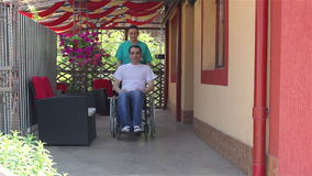 Nurse walking with male patient in a wheelchair stock footage