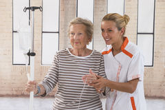 Nurse walking next to a patient with IV drip Stock Images