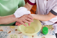 Nurse washes old patient's hands Stock Photo