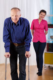 Nurse watches as disabled trying to walk Stock Photo